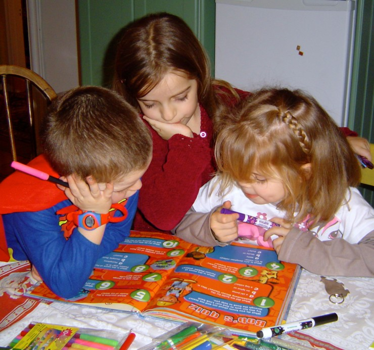 Three children reading a book. Copyright Gretta Schifano