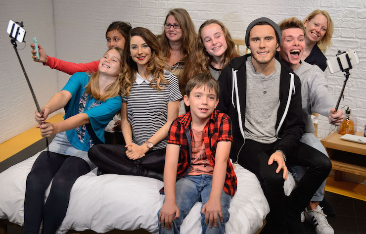 Fans grab a selfie with Zoe Sugg and Alfie Deyes' wax figures in new YouTube themed area at Madame Tussauds London. Copyright Madame Tussauds.