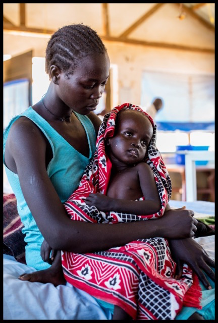 Avpai Agongi with her son Akur Akuer on a bed in the Action Against Hunger Aweil Stabilization Centre, South Sudan. Copyright Andrew Parsons.